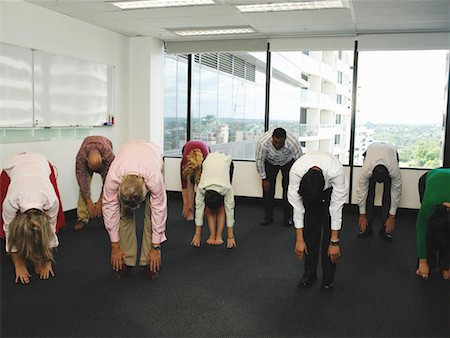 Business colleagues bending over, touching toes in office Stock Photo - Premium Royalty-Free, Code: 613-00999509