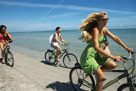 Three young woman riding bicycles on beach, laughing, side view Stock Photo - Premium Royalty-Free, Code: 613-00999888