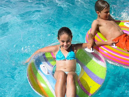 preteen girl wet clothes - Brother and sister (9-12) sitting on inflatables in swimming pool Stock Photo - Premium Royalty-Free, Code: 613-01000308