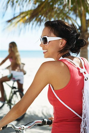 Two young women on bicycles on beach, close-up (focus on foreground) Stock Photo - Premium Royalty-Free, Code: 613-01000401