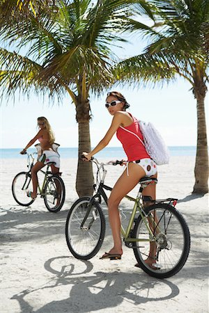 Two young women on bicycles on beach, portrait Stock Photo - Premium Royalty-Free, Code: 613-01000459