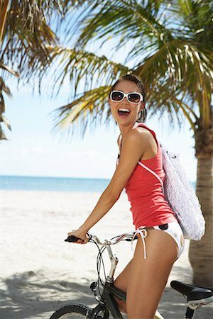 Young woman smiling on bicycle, portrait Stock Photo - Premium Royalty-Free, Code: 613-01000606