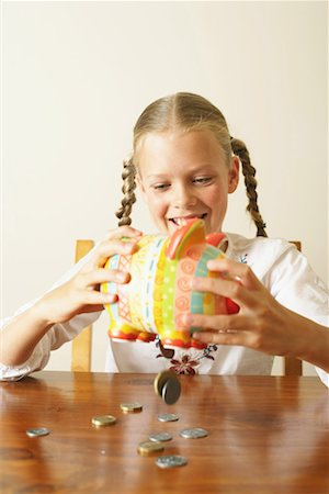 Girl (10-12) emptying piggy bank onto table, smiling Stock Photo - Premium Royalty-Free, Code: 613-01034040