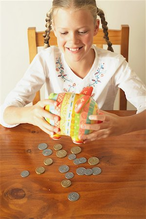 Girl (10-12) emptying piggy bank onto table, smiling, elevated view Stock Photo - Premium Royalty-Free, Code: 613-01034449