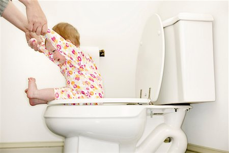 Baby girl (12-15 months) sitting on toilet, holding mother's hands Stock Photo - Premium Royalty-Free, Code: 613-01035217
