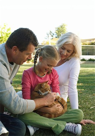 Parents and daughter (10-12) in garden, looking down at cat, smiling Stock Photo - Premium Royalty-Free, Code: 613-01035823