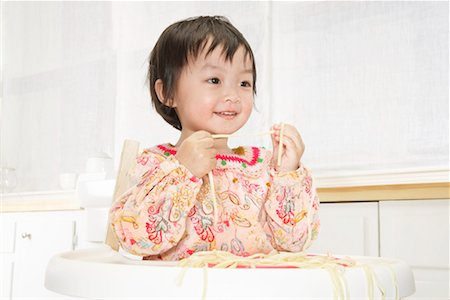 Toddler girl (21-24 months) playing with pasta in high chair, close-up Stock Photo - Premium Royalty-Free, Code: 613-01033619