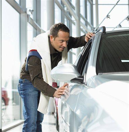 Man looking at car in showroom, smiling Stock Photo - Premium Royalty-Free, Code: 613-01101567