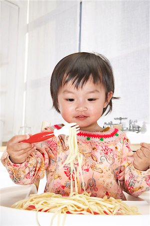 Baby girl (18-24 months) in high chair eating spaghetti with fork Stock Photo - Premium Royalty-Free, Code: 613-01101585