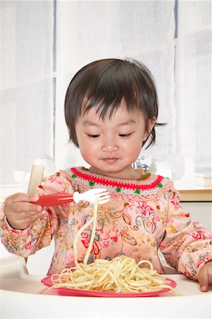 Baby girl (18-24 months) in high chair eating spaghetti with fork Stock Photo - Premium Royalty-Free, Code: 613-01101586