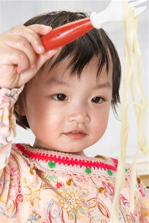 Baby girl (18-24 months) holding up pasta on fork, close-up Stock Photo - Premium Royalty-Free, Code: 613-01101591