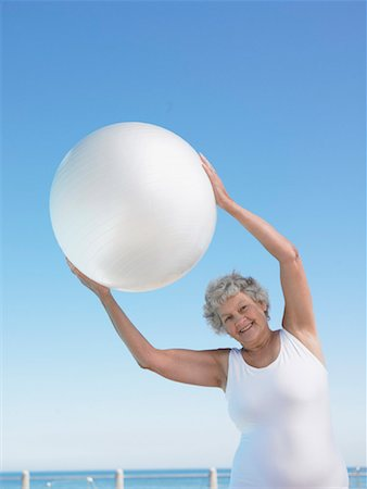 seniors woman in swimsuit - Senior woman holding exercise ball over head, smiling, portrait Stock Photo - Premium Royalty-Free, Code: 613-01102300