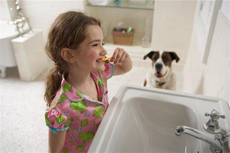 Young girl (8-10) in bathroom brushing her teeth with dog Stock Photo - Premium Royalty-Free, Code: 613-01125281