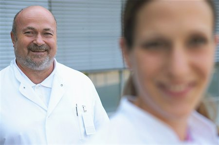 Male and female doctor outdoors, focus on male doctor,smiling, portrait Stock Photo - Premium Royalty-Free, Code: 613-01169210