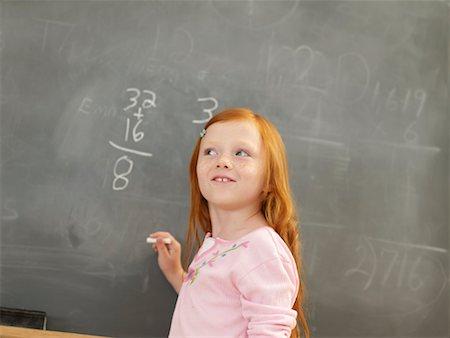 Girl (6-8) standing at blackboard looking up Stock Photo - Premium Royalty-Free, Code: 613-01169278