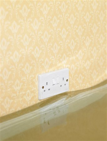 flooded homes - Electric wall outlet reflected in water in flooded living room Stock Photo - Premium Royalty-Free, Code: 613-01187894