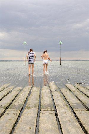 Two teenage girls(12-14), walking on wooden pier, rear view Stock Photo - Premium Royalty-Free, Code: 613-01286149