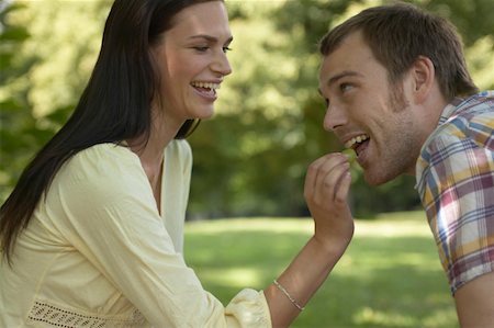 Couple relaxing in park, woman feeding man grape, both laughing Stock Photo - Premium Royalty-Free, Code: 613-01286545
