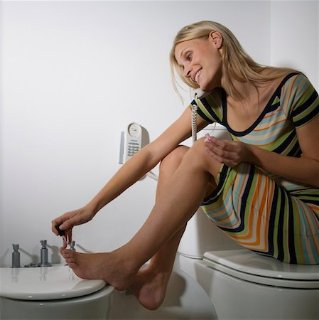 Woman using telephone in bathroom whilst painting nails Stock Photo - Premium Royalty-Free, Code: 613-01287565