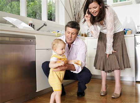 Parents looking at daughter (9-12 months) walking in kitchen Stock Photo - Premium Royalty-Free, Code: 613-01288327