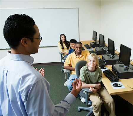 Male teacher talking to students (11-13) sitting at computers Stock Photo - Premium Royalty-Free, Code: 613-01289309