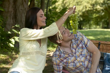 Couple relaxing in park, woman feeding man grapes, both laughing Stock Photo - Premium Royalty-Free, Code: 613-01294722