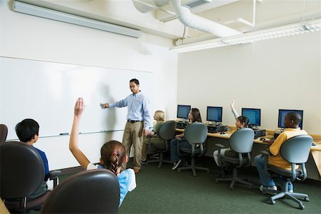 Male teacher talking to students (9-13) sitting at computers Stock Photo - Premium Royalty-Free, Code: 613-01293357