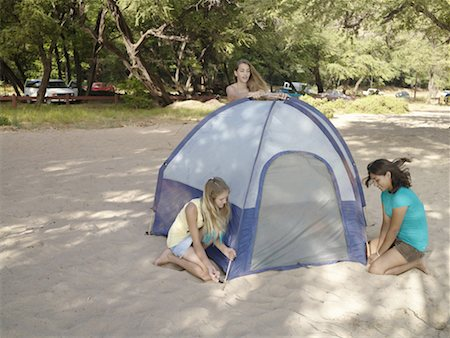 Teenage girls (12-14) pitching tent at beach Stock Photo - Premium Royalty-Free, Code: 613-01370224