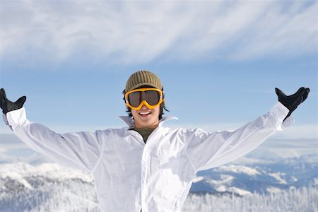 Teenage (17-19) male snowboarder spreading arms wide, portrait Stock Photo - Premium Royalty-Free, Code: 613-01388452