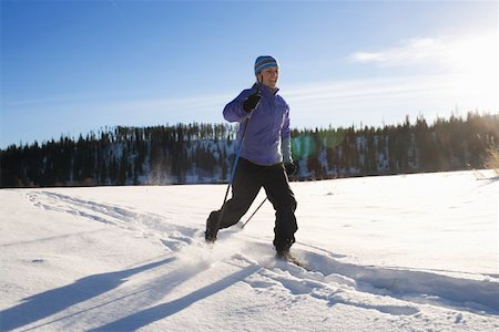 Woman sprinting over snow, rear view, winter Stock Photo - Premium Royalty-Free, Code: 613-01388461