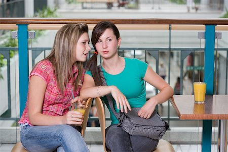 Teenage girls (15-17) whispering at cafe table in shopping centre Stock Photo - Premium Royalty-Free, Code: 613-01388639