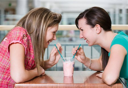 Teenage girls (15-17) sharing drink at cafe table, smiling, profile Stock Photo - Premium Royalty-Free, Code: 613-01388642