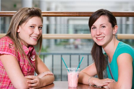 Teenage girls (15-17) sharing drink at cafe table, smiling, portrait Stock Photo - Premium Royalty-Free, Code: 613-01388643