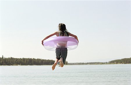 preteen girl wet clothes - Girl (11-13) jumping into lake with inner tube, rear view Stock Photo - Premium Royalty-Free, Code: 613-01383166