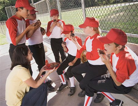 Mother giving cupcakes to boys (9 12) in baseball dugout Stock Photo - Premium Royalty-Free, Code: 613-01394160