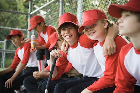 Baseball players (9-14) in dugout (focus on two boys smiling) Stock Photo - Premium Royalty-Free, Code: 613-01394176