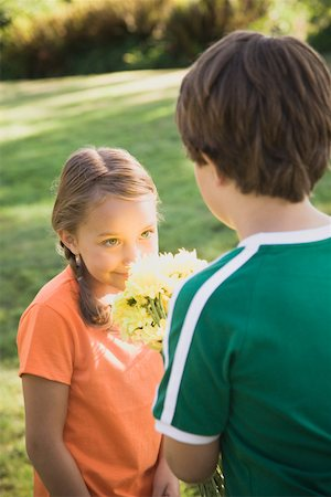 Boy (6-8) giving bouquet of flowers to girl (6-8) Stock Photo - Premium Royalty-Free, Code: 613-01394622