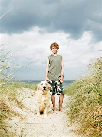 preteen  smile  one  alone - Boy (10-12) standing on beach with dog on lead, smiling, portrait Stock Photo - Premium Royalty-Free, Code: 613-01394789
