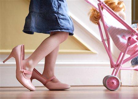 Girl (3-5) wearing adult shoes, pushing doll in pram, low section Stock Photo - Premium Royalty-Free, Code: 613-01392392