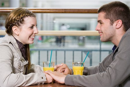Teenage couple (15-17) holding hands in cafe, side view Stock Photo - Premium Royalty-Free, Code: 613-01393027
