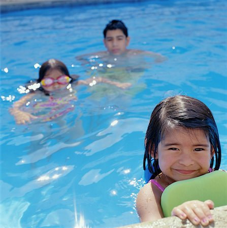 preteen girl wet clothes - Boy (12-14) and two girls (4-7) swimming in pool (selective focus) Stock Photo - Premium Royalty-Free, Code: 613-01401999