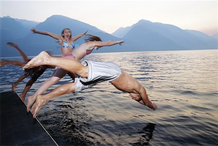Group of teenagers (15-17) diving into lake Stock Photo - Premium Royalty-Free, Code: 613-01472184