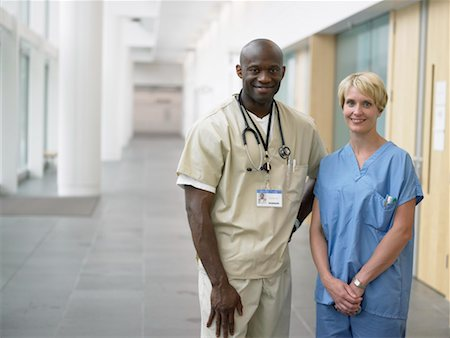 Two surgeons standing in hospital corridor, smiling, portrait Stock Photo - Premium Royalty-Free, Code: 613-01528955