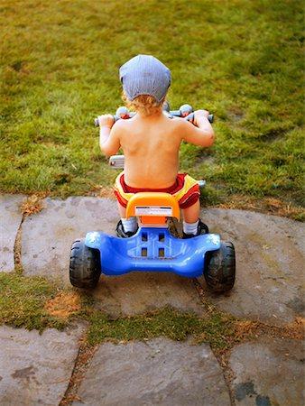 Boy (2-4) riding on toy car, rear view Stock Photo - Premium Royalty-Free, Code: 613-01534260