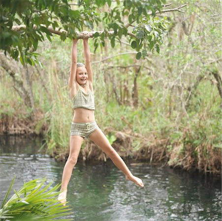 preteen  smile  one  alone - Girl (9-11) hanging from tree, above water, smiling, portrait Stock Photo - Premium Royalty-Free, Code: 613-01534793