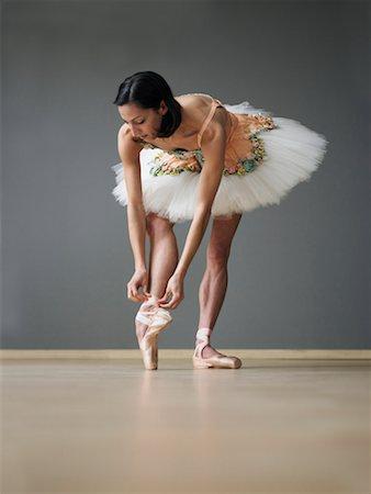 Young female ballerina adjusting ballet slipper Stock Photo - Premium Royalty-Free, Code: 613-01535050