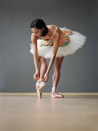 Young female ballerina adjusting ballet slipper Stock Photo - Premium Royalty-Free, Code: 613-01535050