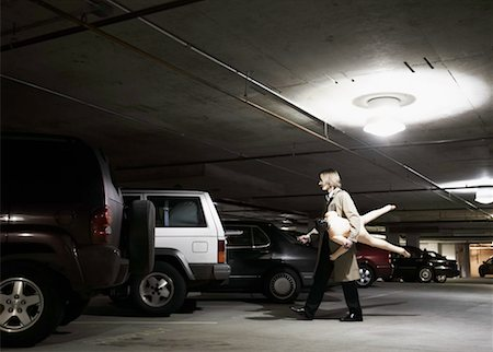 person walking on parking lot - Young businessman carrying blow- up doll in parking garage, side view Stock Photo - Premium Royalty-Free, Code: 613-01536524