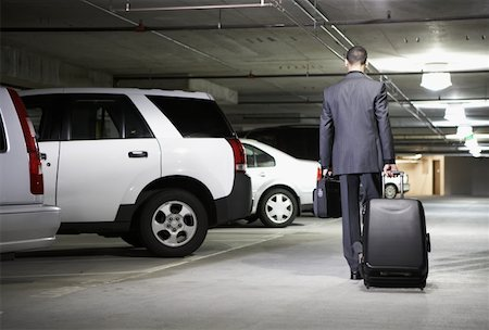 person walking on parking lot - Young businessman with luggage in parking garage, rear view Stock Photo - Premium Royalty-Free, Code: 613-01536544