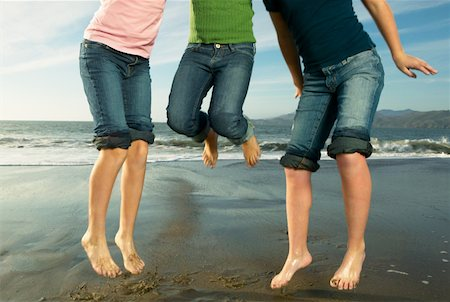 preteen girl wet clothes - Three girls (10-12) on beach jumping in air, low section Stock Photo - Premium Royalty-Free, Code: 613-01530480